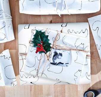 A bird's eye view of a gift wrapped using twine, holly and homemade wrapping paper and placed on a wooden worktop.