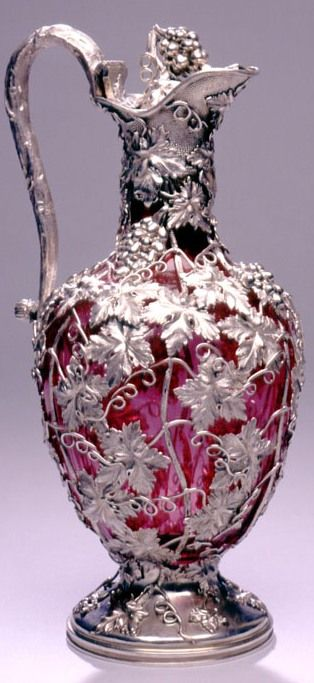 "Reily & Storer A glorious silver mounted pale ruby glass Claret Jug, London, 1840. The  ruby glass is encased in a naturalistic design of cast and chased fruiting vines. This style was popular from about 1830 onwards and was the artistic 'antidote' to the more formal and rigid ""Pompeian grandeur"" of the Neoclassical Revival period that preceded it."