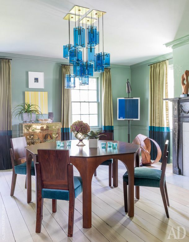 Exquisite dining room with an architectural table and brass chest, punctuated with doses of turquoise