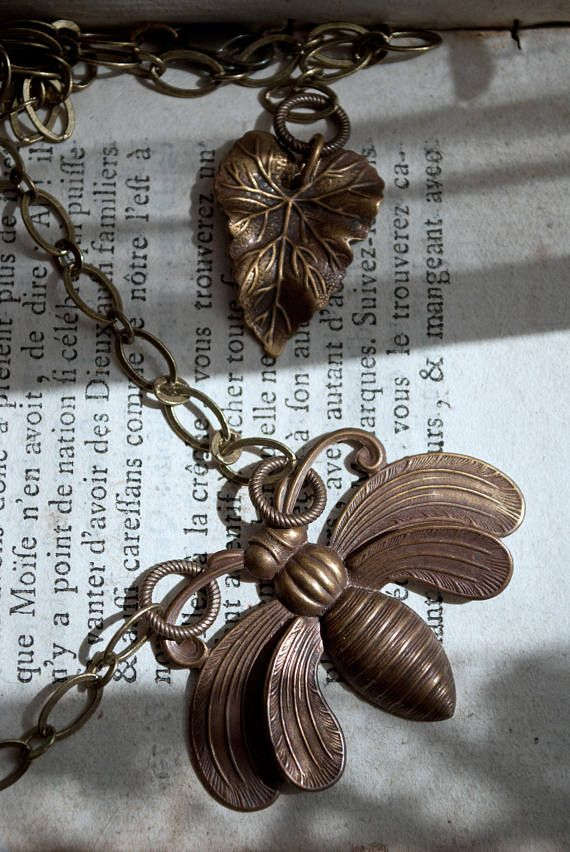 A lovely necklace and small earrings set in natural colors. The brass has been carefully aged by hand through a natural process. The focal point is a beautiful large bee. Added to the special larger chain is a flower bud featuring an antique Aurora Borealis crystal. Its clear, but shimmers rainbow colors when the light catches it. The end of the chain is adorned with a highly detailed leaf. Secure lock. The earrings have lever backs and very detailed sunflowers which are about 1 cm each. The…