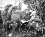 Lieutenant R. A. Tilgham studying a map with his Marines, western Iwo Jima, Japan, 1945