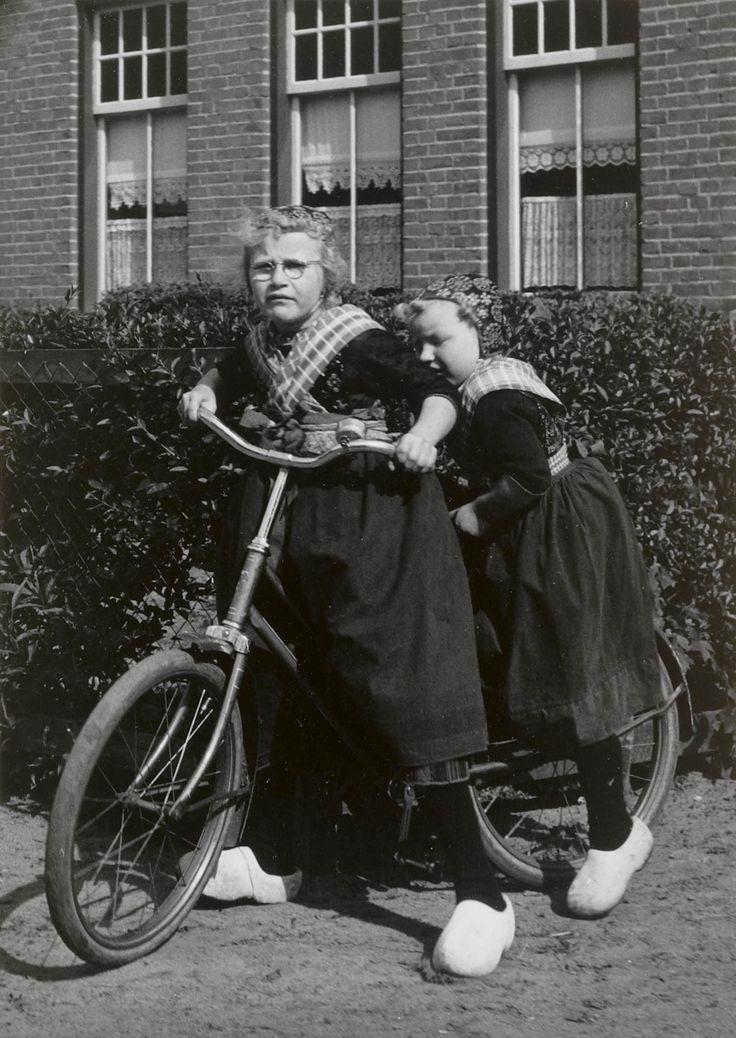 Twee meisjes in Staphorster streekdracht op een fiets. Beiden zijn gekleed in daagse dracht. 1960 #Overijssel #Staphorst
