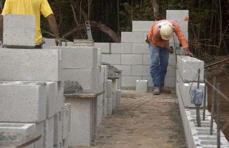 Masonry construction workers building cinderblock wall