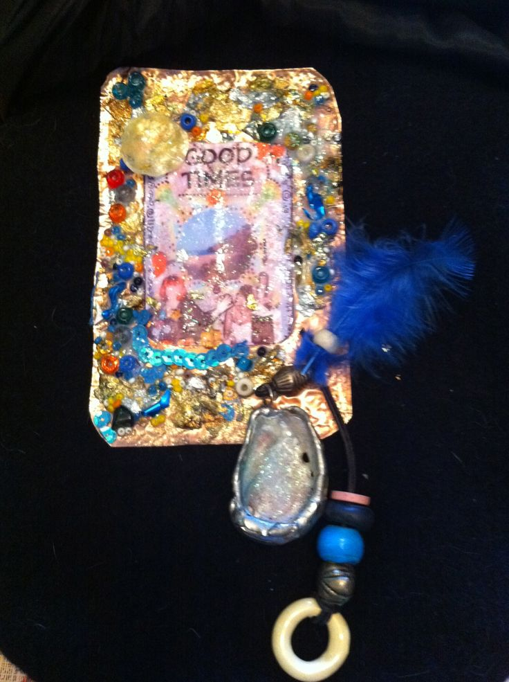 Metal jewellery with shells, beads, feather & image under resin