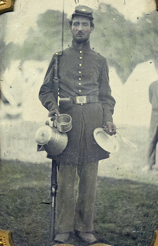 ARMED AND READY FOR FOOD, this soldier pauses for his photograph with a bayonet fixed on his rifle musket and a handful of tin-ware and utensils, including the essential coffee pot. Perhaps coming off evening parade, he wears a frock coat sans shoulder scales. The rectangular Model 1851 belt plate suggests he is a non-commissioned officer.