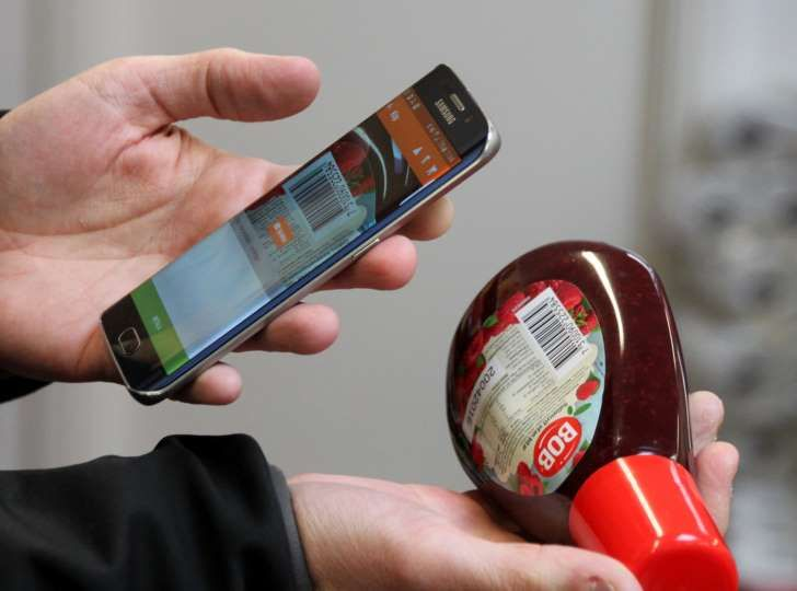 Swedish IT entrepreneur Robert Ilijason shows how to use a cell phone to scan a purchase at the no-staff, app shop in the southern Sweden village of Viken in this photo dated Jan. 27, 2016. Customers to the new general store need to register and download a cell phone app, then customers simply use their cellphones to unlock the door with a swipe of the finger and scan their purchases then they get charged for their purchases in a monthly invoice.