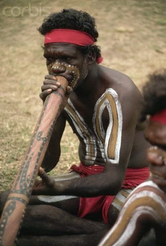Australia | An aborigine with painted body plays the didgeridoo in Northern Territory
