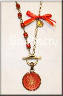 Colar comprido com corrente bronze, contas de vidro, aplicações de metal e cetim. Com medalhão pintado à mão.