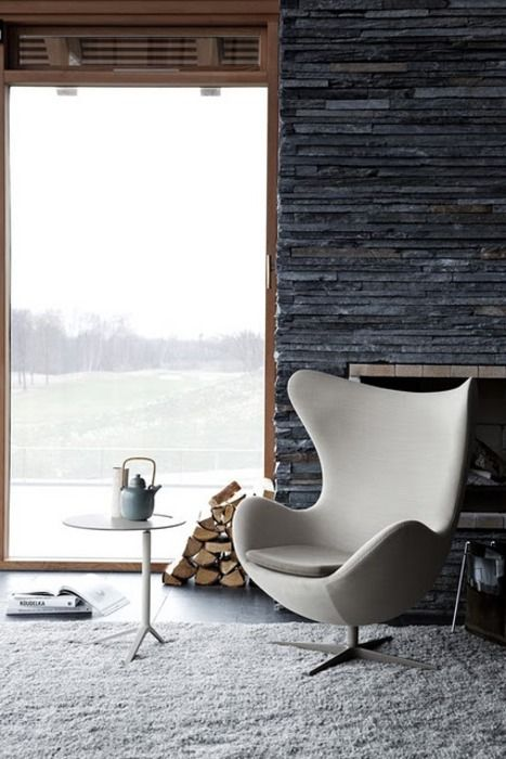 Arne Jacobsen Egg chair in white by slate fire place. A great spot for reading.