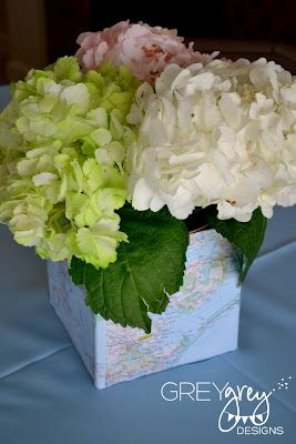 Simple yet beautiful floral centerpiece with map on vase for travel themed wedding