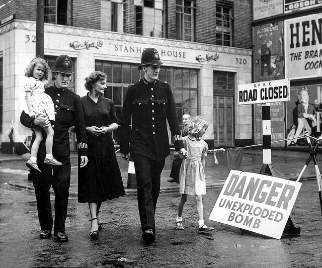 2 policemen escorting 2 young girls & their mother to safety, past area closed off due to recently discovered 2,500 lb. German bomb, which was dropped in 1941 (during WWII), shortly before it was defused. 1948.