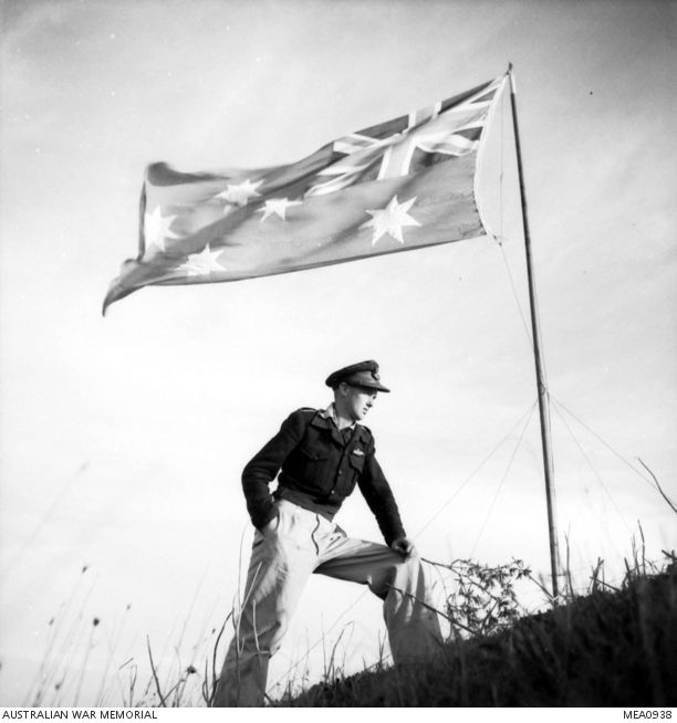 Italy. 1943. Informal portrait of Flying Officer H. Hannaford of Blackwood, SA, a fighter bomber pilot with the Desert Harassers No. 450 Squadron RAAF, under the Australian flag. The flag was ...