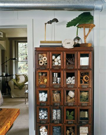 An antique seed-packet cabinet with glass-front drawers