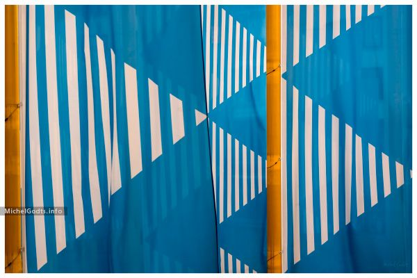 Yellow flagpoles holding blue and white flags, part of a permanent art installation in Brussels, Belgium. Abstract realism photography prints for art collectors or for a wall decor.
