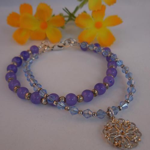 Een armband met de kleuren van een weide vol wilde lavendel in de Provence.  Ook het bedeltje herinnert aan wiegende lavendelbloemetjes onder een blauwe hemel.