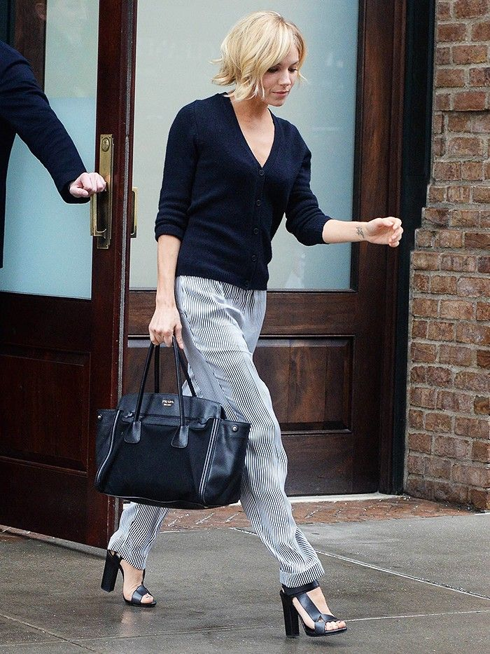 Sienna Miller in a Chinti & Parker Elbow Patch Cardigan; Belstaff trousers; Pierre Hardy sandals: & a Prada tote