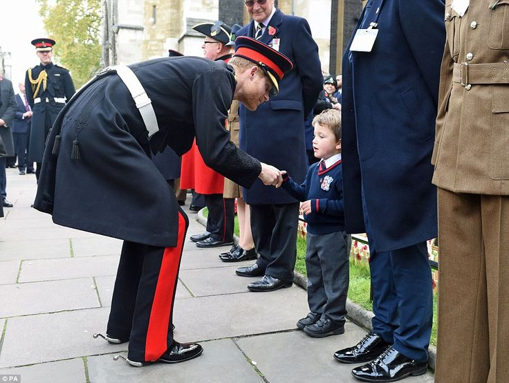 Prince Harry shakes hands with a child at Westminster Abbey's Field of Remembrance where h...