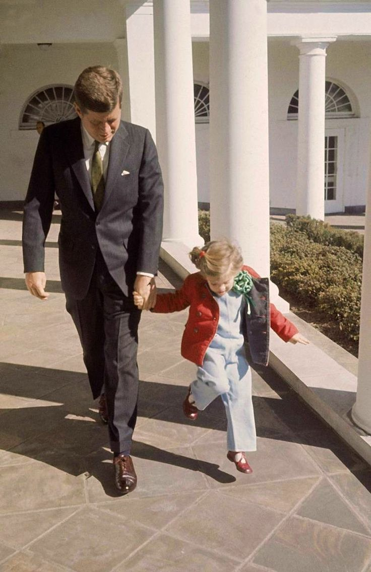 President Kennedy walking hand-in-hand with daughter Caroline on St. Patrick's Day at the White House ~ March 17th, 1961  Check out the green tie and Caroline's shamrock :-)