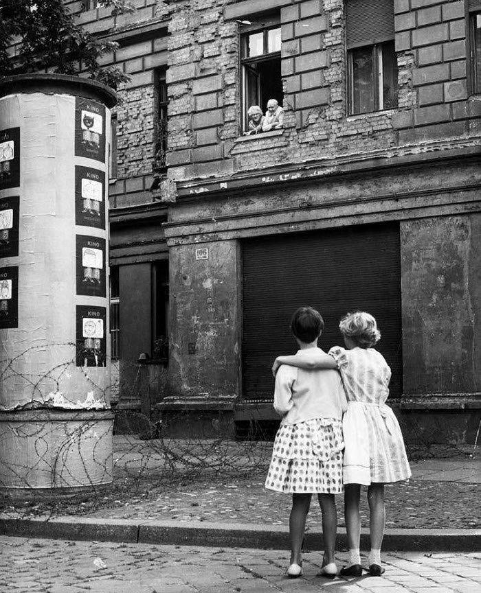 Граница ФРГ и ГДР.  Две девочки на территории ФРГ разговаривают со своими бабушкой и дедушкой в окне дома на территории ГДР, отделенной баррикадой из колючей проволоки, 14 августа 1961 года.