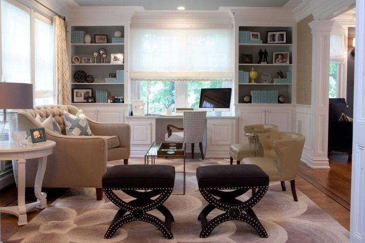 This midcentury modern living room features white built-in bookshelves, a neutral area rug with swirl patterns, white crown molding, wainscoting and other architectural trim. A curved beige sofa provides seating, as does a pair of stylish brown stools for occasional seating.
