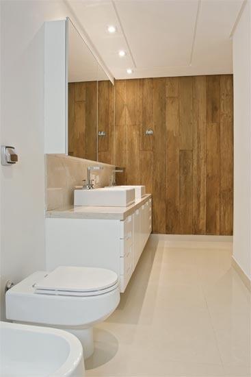 Amplo e iluminado, o banheiro ganhou uma charmosa parede revestida de madeira de demolição. O piso, as paredes do boxe e os rodapés são de porcelanato claro. A bancada é de mármore crema marfil e os armários, de MDF laqueado.