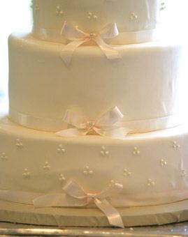 White Fondant Wedding Cake with Bows. The elegant, white buttercream-frosted cake by Montecito Confections in Santa Barbara had a different flavor for each tier.