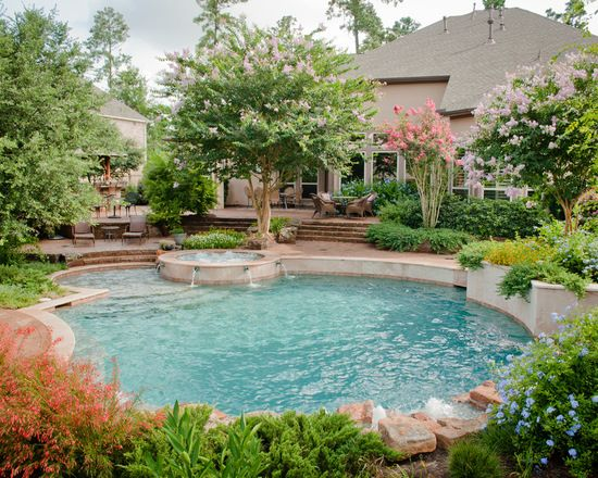 Example of a large classic backyard round pool design with for Pool design examples