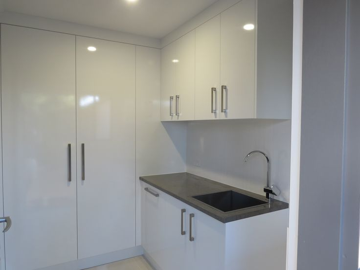 Laundry: With broom cupboard, storage cupboards with ADJ shelves and a pull out basket drawer.  Tops- Laminex 'Petra Stone' diamond gloss 33mm Doors- Laminex 'Polar White' melamine silk with 1mm PVC impact edge Handles- Artia 'Axis'