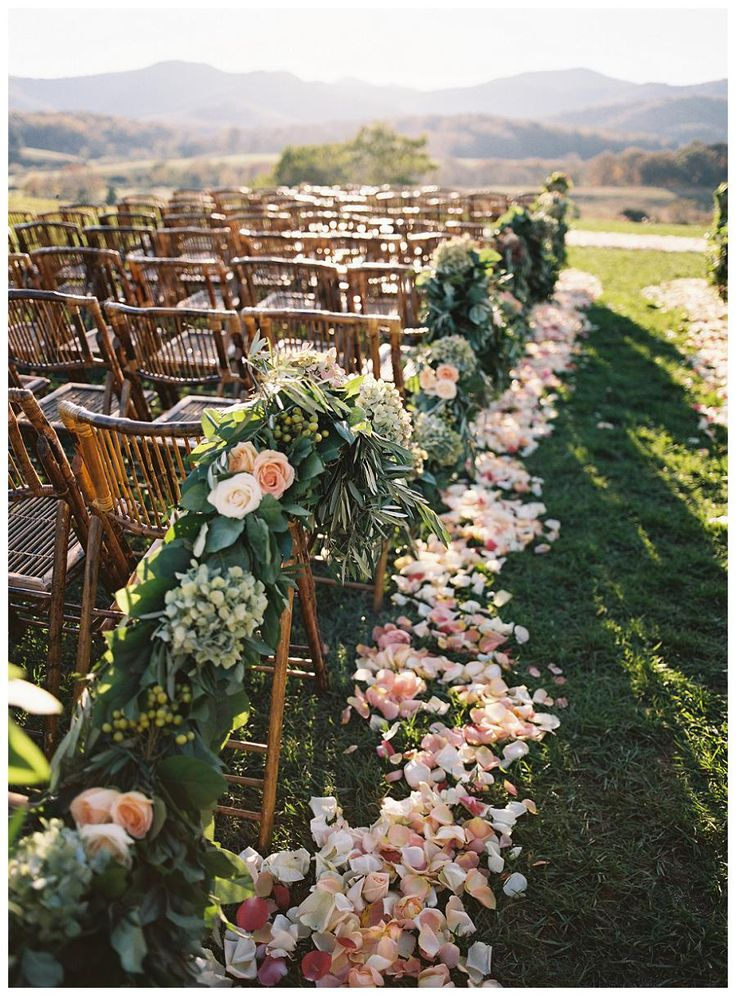 Wedding Ceremony Decor: Bamboo chairs with flower petal aisle on the Ceremony Lawn at Pippin Hill Farm & Vineyards near Charlottesville, VA. Lush floral and greenery garland with flower petal aisle by Beehive Events and image by Eric Kelley.