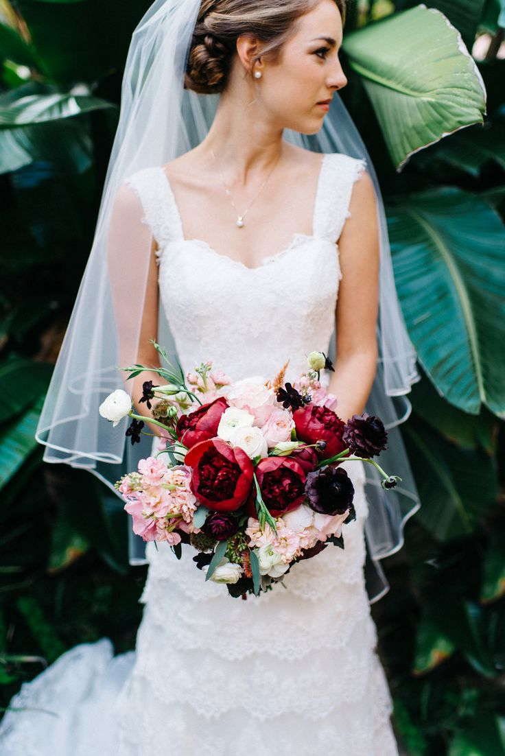 Rich fall colors make up this bridal bouquet of red charm peonies, peach stock, chocolate cosmos, peach celosia, Kiera garden roses, burgundy ranunculus, pink lisianthus and white majolik spray roses. Photo by: www.rebbeccareadphotography.com