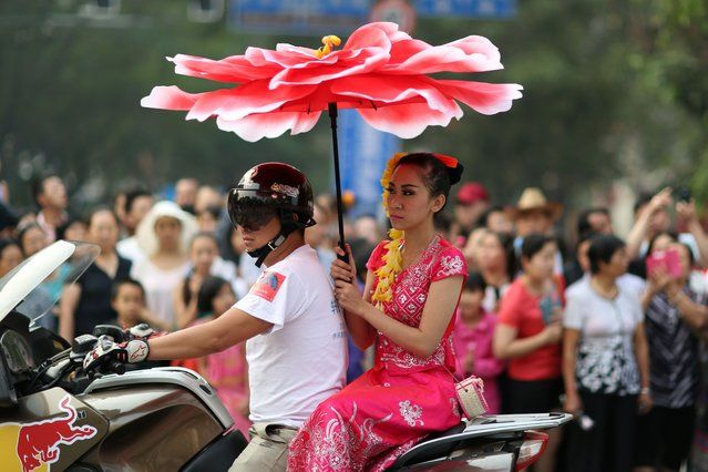 A woman takes part in a parade to celebrate the Dai ethnic group new year in Jinghong, southwest China's Yunnan province on April 14, 2014. A series of celebrations kick off on April 13 to welcome the coming year of 1376 in the Dai ethnic group calendar, with people dancing and parading on the streets of Jinghong municipality in China's Xishuangbanna Dai Autonomous Prefecture. (Photo by AFP Photo)