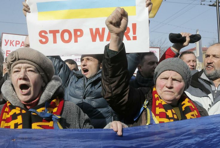 People hold banners and shout during a rally against the conflict between Russia and Ukraine near the Russian embassy in Kiev, Ukraine, Friday, March 7, 2014.