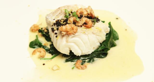 Gepocheerde kabeljauw, spinazie, amandel, zwarte olijf en witte wijnsaus - Recept | VTM Koken