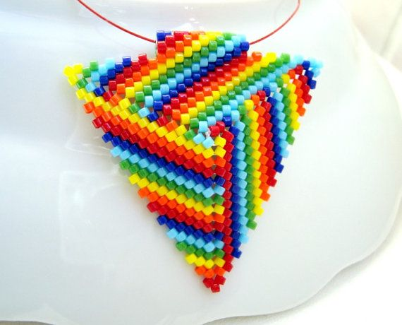"""Color pattern: This stunning triangle pendant is woven in peyote stitch, using Japanese delica beads in rainbow colors. The sides of the triangle are 1.1/2"""" (4cm)long."""
