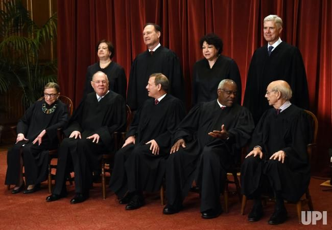 Members of the U.S. Supreme Court pose for a group photograph at the Supreme Court building in Washington, DC on June 1 2017. Front row.…
