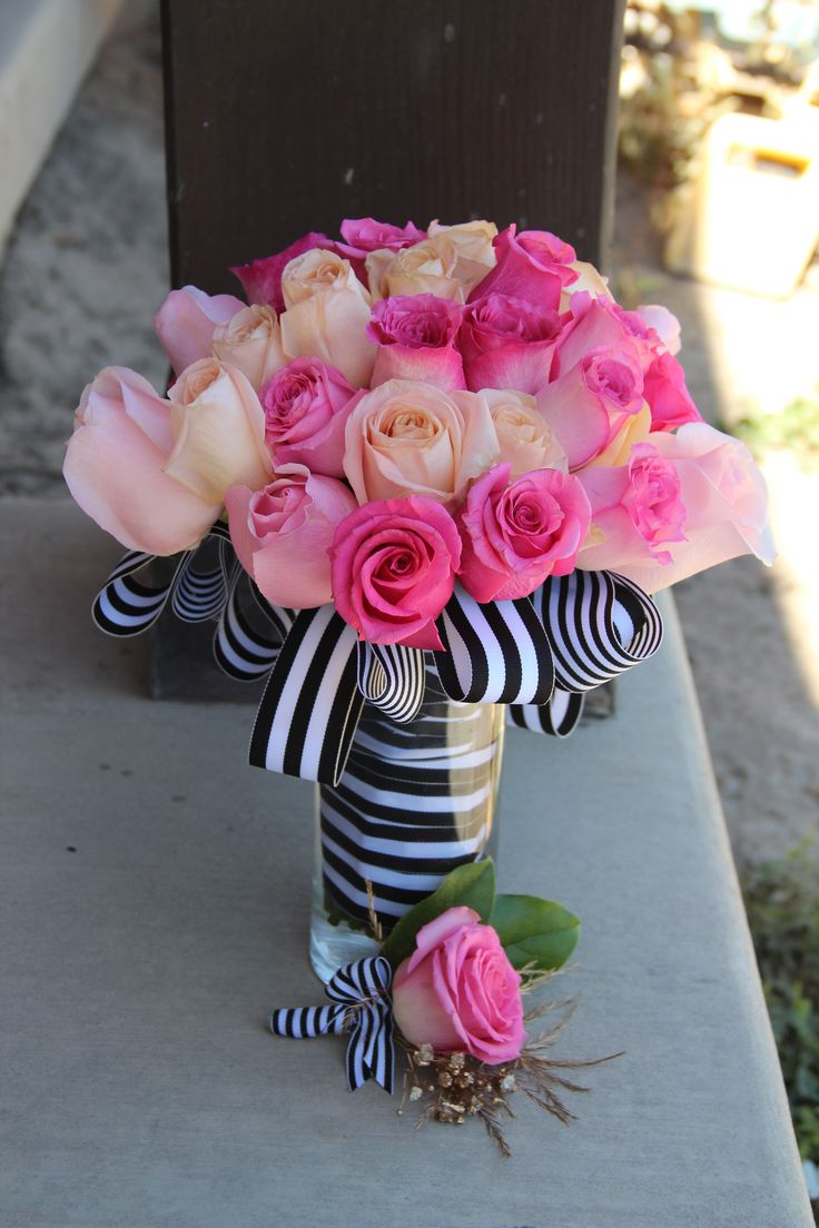A bouquet of roses alone inspired by Kate Spade.  This wedding bouquet features roses in peach and three different shades of pink.  The boutonnière is a single rose with babys breath sprayed in gold accented with salal leaves.  Black and white striped ribbon in two different widths perfectly finish this bouquet and grooms boutonnière.  #katespadewedding