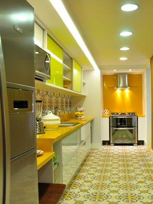 """A disposição se assemelha à letra """"L"""" ao aproveitar duas paredes para colocar fogão, pia, geladeira e armários. Permite boa circulação e contribui na organização do espaço."""