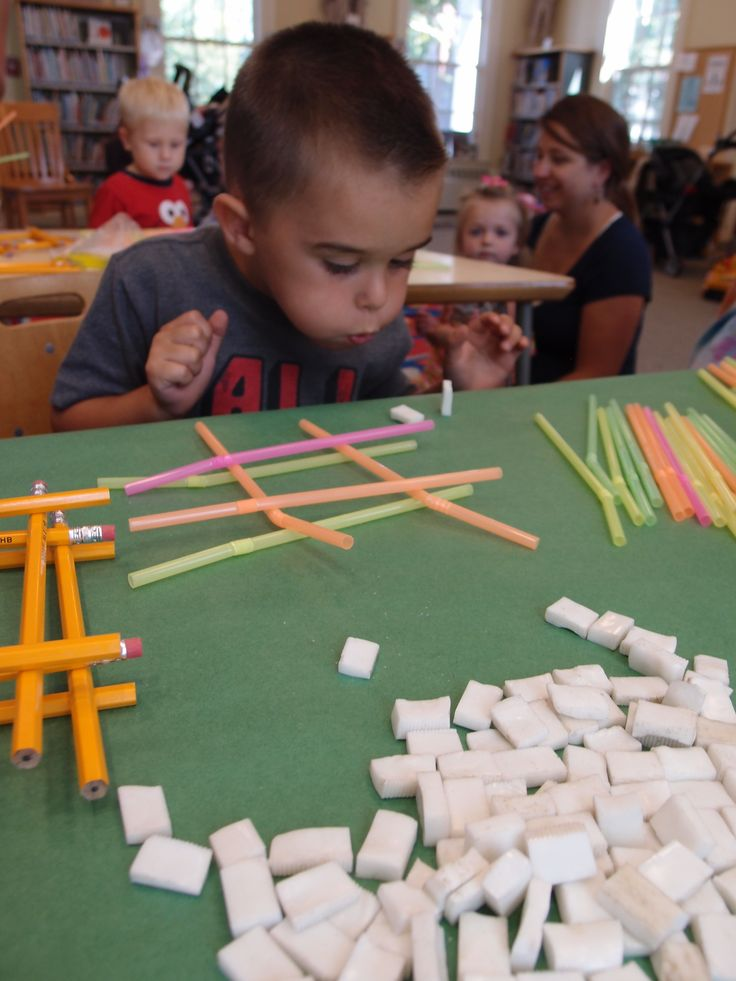 Three Little Pigs build a house activity using straws, pencils, and tiles.