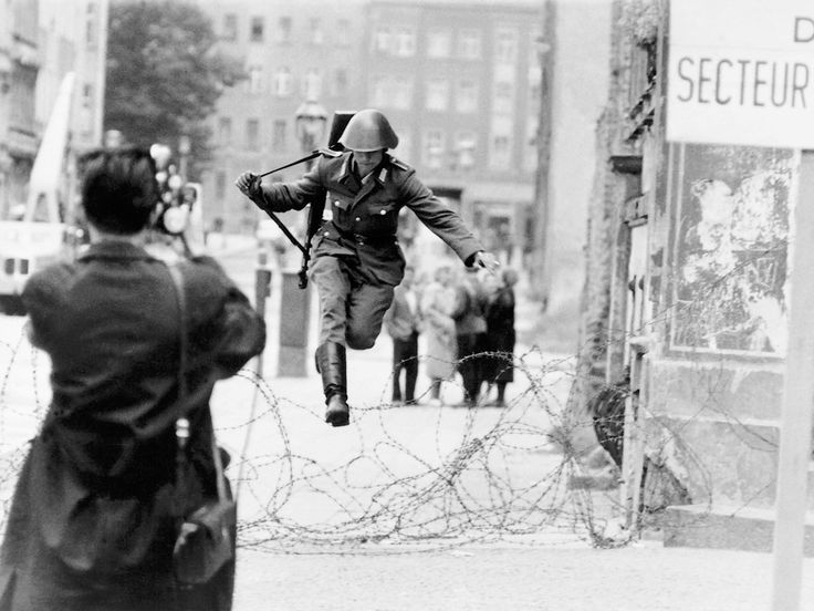 429 An East German border guard defecting into West Germany during the construction of the Berlin Wall in 1961
