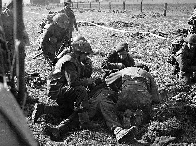 Canadian soldier wouded by German sniper fire while attempting to cross over the southern dyke of the Afwalnings Canal. 7 Apr. 1945, Laren, Netherlands.
