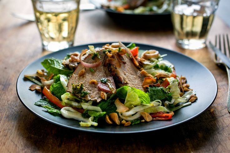 There are a lot of ingredients in this bright and bold-tasting pork salad recipe; they add up to a vibrant dish you can serve warm or at room temperature to a spice-loving crowd Lean pork tenderloin is marinated with chiles, ginger root and cilantro, grilled or broiled, then combined with cabbage, fresh herbs and nuts and coconut for richness A bit of reserved marinade serves as the dressing