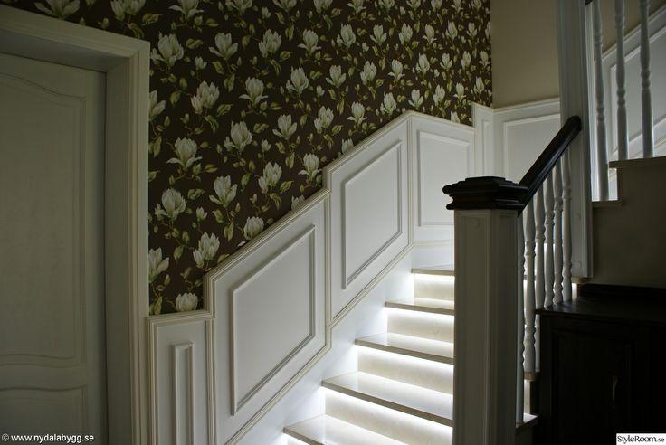 Styleroom hall hos Nydalabygg. Liknande med bröstpanel och breda pålar trappräcke, samt mönstrad tapet. Snygg belysning med hjälp av led-ljuslinga under (utanpå) trappstegen.