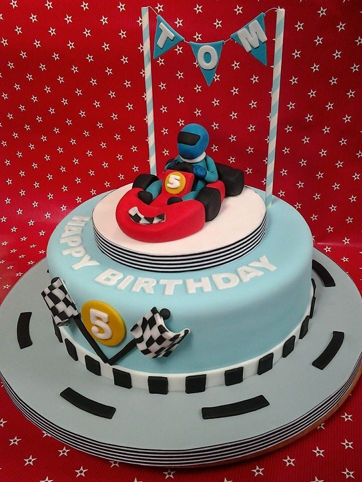 Go kart cake with fondant go kart and racing driver with flags.