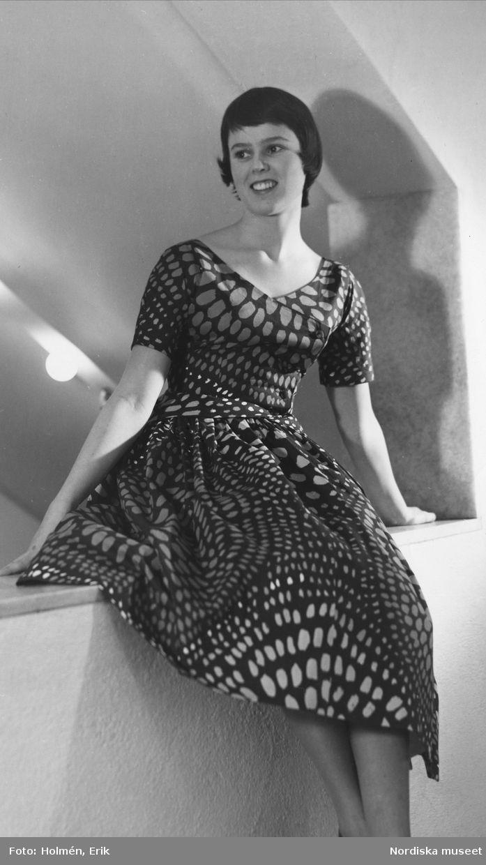 Modebild från Nordiska Kompaniet 1955. Viola Gråsten - utställning. Modell klädd i mörk klänning med abstrakt mönster.