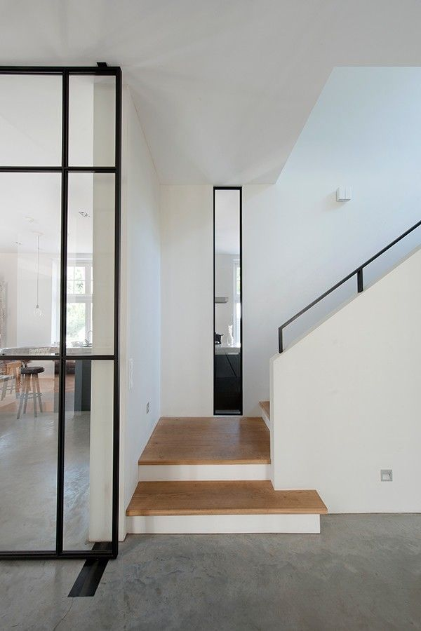Thin black frame railings, doors & window frames by Vocus Architecten.