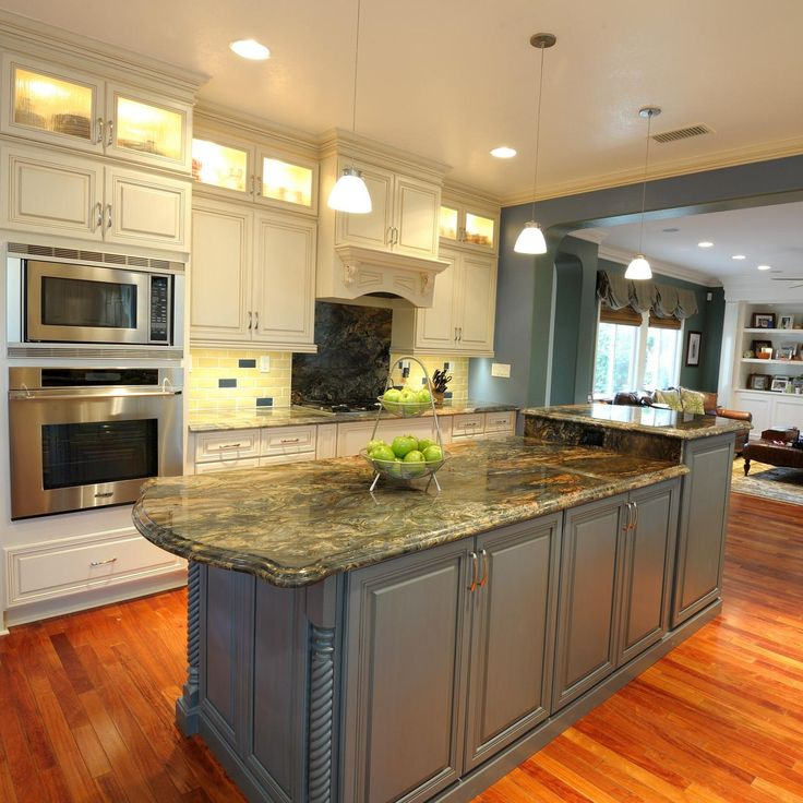 In this lovely transitional kitchen, style works hand in hand with functionality. Transom cabinets provide extra storage and visual interest, with their interior lighting and frosted glass doors. A slate blue island adds a hit of color as well as a much-needed work space.