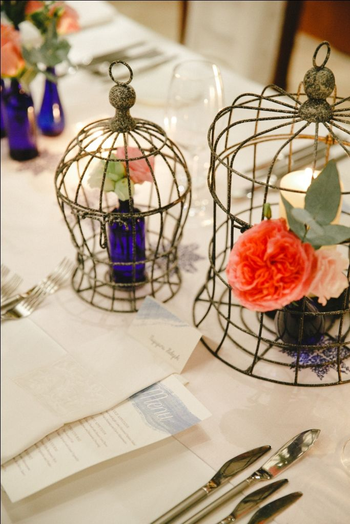 Dining table centerpiece arranged in birdcage and blue bottle