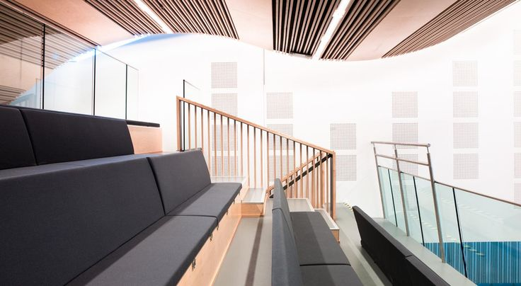 The wave of the wooden ceiling creates an intimate space in the back and rises dramatically upwards like clouds in the sky. Artwork is integrated in the walls, ceiling and the flooring as a part of the building.