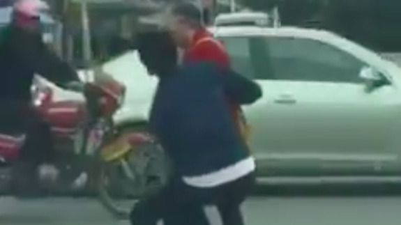 China-knight- carries elderly woman across the street.