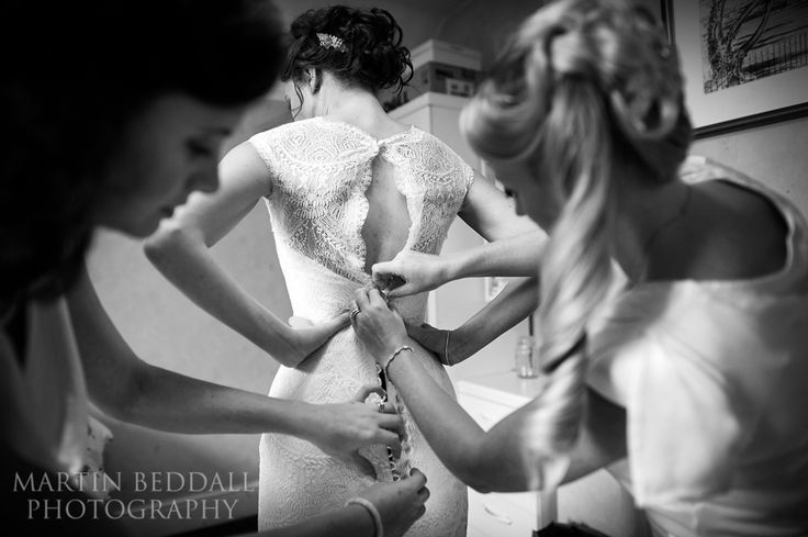reportage wedding photography close up view as bridesmaids tie back of the…